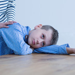 Autistic boy laying on a table